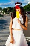 Härlig blandras- asiatisk kines/Caucasian ung kvinna Glassflicka som äter gul eskimo glass på gatan arkivbilder