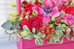 Härlig blom- ordning av röda, rosa och burgundy blommor i en rosa träask royaltyfria foton