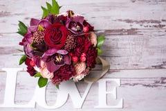 Härlig blom- ordning, på den sjaskiga vita trätabellen med utrymme för text Fotografering för Bildbyråer