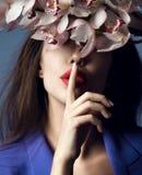 härlig blommaflickaorchid Framsida för skönhetmodellkvinna på purpurfärgad bakgrund royaltyfri foto