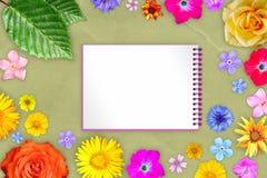 Härlig blommaram med förskriftsboken i mitt på gul bakgrund för kraft papper Blom- sammansättning av vår- eller sommarblommor arkivfoton
