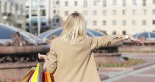 Härlig blond caucasian kvinna för tillbaka sikt i solglasögon som vinkar handen för att stoppa bilen som förbigår lager videofilmer