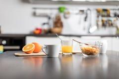 Härlig blond caucasian kvinna som poserar i hennes kök, medan dricka, kaffe eller te och äta ett sunt frukostmål mycket av ce royaltyfria bilder