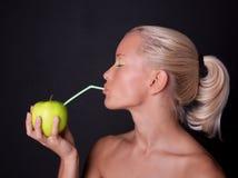 härlig blond dricka fruktsaftkvinna för äpple Royaltyfria Bilder