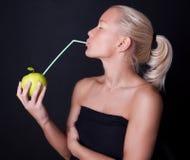 härlig blond dricka fruktsaftsugrörkvinna Arkivfoton