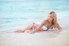 Härlig blond europeisk yrkesmässig modellflicka som ligger på sandigt Arkivfoto