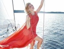 Härlig blond flicka i bra form med röda kanter för långt mörkt hår och för solbränd hud i placering för lögn för hatt för modesim Royaltyfri Foto