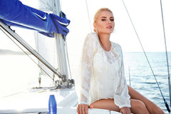 Härlig blond flicka i bra form med röda kanter för långt mörkt hår och för solbränd hud i placering för lögn för hatt för modesim Royaltyfria Bilder