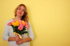 Härlig blond flicka i den blåa klänninginnehavbuketten av gula och rosa rosor på enguling bakgrund royaltyfria bilder