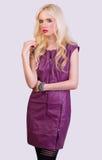 Härlig blond flicka i den violetta klänningen Royaltyfri Bild