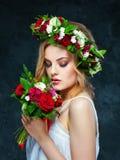Härlig blond flicka i en krans av blommor Fotografering för Bildbyråer