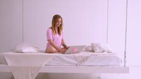 Härlig blond flicka i en rosa T-tröja av det europeiska utseendet som sitter på sängen med en bärbar dator Arbeten hemma prata stock video