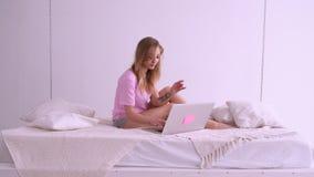 Härlig blond flicka i en rosa T-tröja av det europeiska utseendet som sitter på sängen med en bärbar dator Arbeten hemma prata arkivfilmer