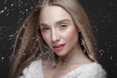 Härlig blond flicka i en vinterbild med snö Härlig le flicka arkivfoton