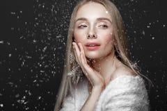 Härlig blond flicka i en vinterbild med snö Härlig le flicka royaltyfria bilder