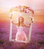 Härlig blond flicka i ett fält av lavendel Arkivfoton