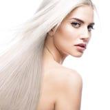 Härlig blond flicka i flyttning med ett perfekt slätt hår och klassiskt smink Härlig le flicka royaltyfria foton