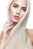 Härlig blond flicka i flyttning med ett perfekt slätt hår och klassiskt smink Härlig le flicka royaltyfri foto