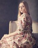 Härlig blond flicka i lång klänning i vardagsrum Royaltyfria Foton