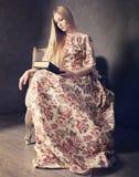 Härlig blond flicka i lång klänning i vardagsrum Arkivbild