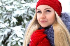 Härlig blond flicka i röd hatt och handskar royaltyfri foto