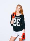Härlig blond flicka i röda boxninghandskar som poserar på en vit bakgrund Hon lyftte en arm inomhus varm färg royaltyfri bild