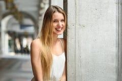 Härlig blond flicka i stads- bakgrund Arkivbild