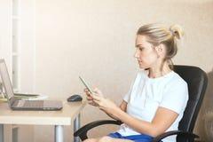 Härlig blond flicka med en hemmastadd smartphone arkivfoton