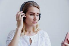 Härlig blond flicka med hörlurar på en ljus bakgrund Hon tycker om att lyssna till musik och att ha gyckel royaltyfri fotografi