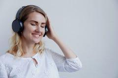 Härlig blond flicka med hörlurar på en ljus bakgrund Hon tycker om att lyssna till musik och att ha gyckel arkivfoton