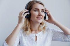 Härlig blond flicka med hörlurar på en ljus bakgrund Hon tycker om att lyssna till musik och att ha gyckel arkivbilder