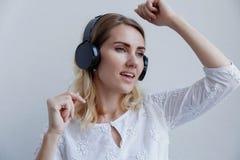 Härlig blond flicka med hörlurar på en ljus bakgrund Hon tycker om att lyssna till musik, att sjunga och att ha gyckel royaltyfri fotografi