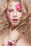 Härlig blond flicka med krullning och en blom- modell på framsidan Abstrakt naturliga bakgrunder Arkivbild