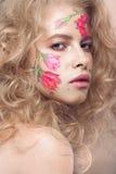 Härlig blond flicka med krullning och en blom- modell på framsidan Abstrakt naturliga bakgrunder Arkivfoto