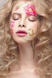 Härlig blond flicka med krullning och en blom- modell på framsidan Abstrakt naturliga bakgrunder Arkivbilder