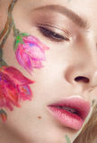 Härlig blond flicka med krullning och en blom- modell på framsidan Abstrakt naturliga bakgrunder Royaltyfri Foto