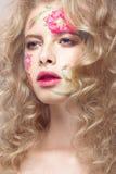 Härlig blond flicka med krullning och en blom- modell på framsidan Abstrakt naturliga bakgrunder Royaltyfria Foton