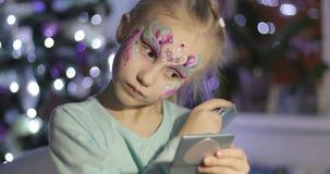 Härlig blond flicka med ljus makeup som ser i en liten spegel och borstar hennes skrapa för hår lager videofilmer