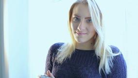 Härlig blond flicka med minnestavlan arkivfilmer
