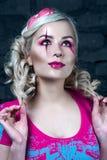 Härlig blond flicka med två råttsvansar, med idérikt dockasmink: rosa glansiga kanter, bärande rosa skelett- klänning för välsign Royaltyfri Bild