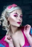 Härlig blond flicka med två råttsvansar, med idérikt dockasmink: rosa glansiga kanter, bärande rosa skelett- klänning för välsign Arkivbilder