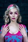 Härlig blond flicka med två råttsvansar, med idérikt dockasmink: rosa glansiga kanter, bärande rosa skelett- klänning för välsign Royaltyfria Foton
