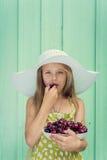Härlig blond flicka på en bakgrund av turkosväggen i den vita hattinnehavplattan med körsbäret royaltyfri bild