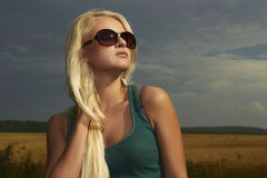 Härlig blond flicka på field.beautyen woman.sunglasses Arkivbild
