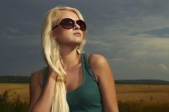 Härlig blond flicka på field.beautyen woman.sunglasses Arkivbild