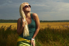 Härlig blond flicka på field.beautyen woman.sunglasses Arkivbilder