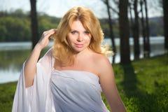 Härlig blond flicka på flodbanken arkivbilder
