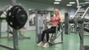 Härlig blond flicka som är förlovad i idrottshallen inomhus lager videofilmer