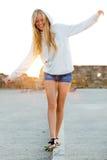 Härlig blond flicka som balanserar på en trottoarkant i staden Fotografering för Bildbyråer
