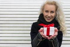 Härlig blond flicka som ger en gåva Royaltyfria Bilder